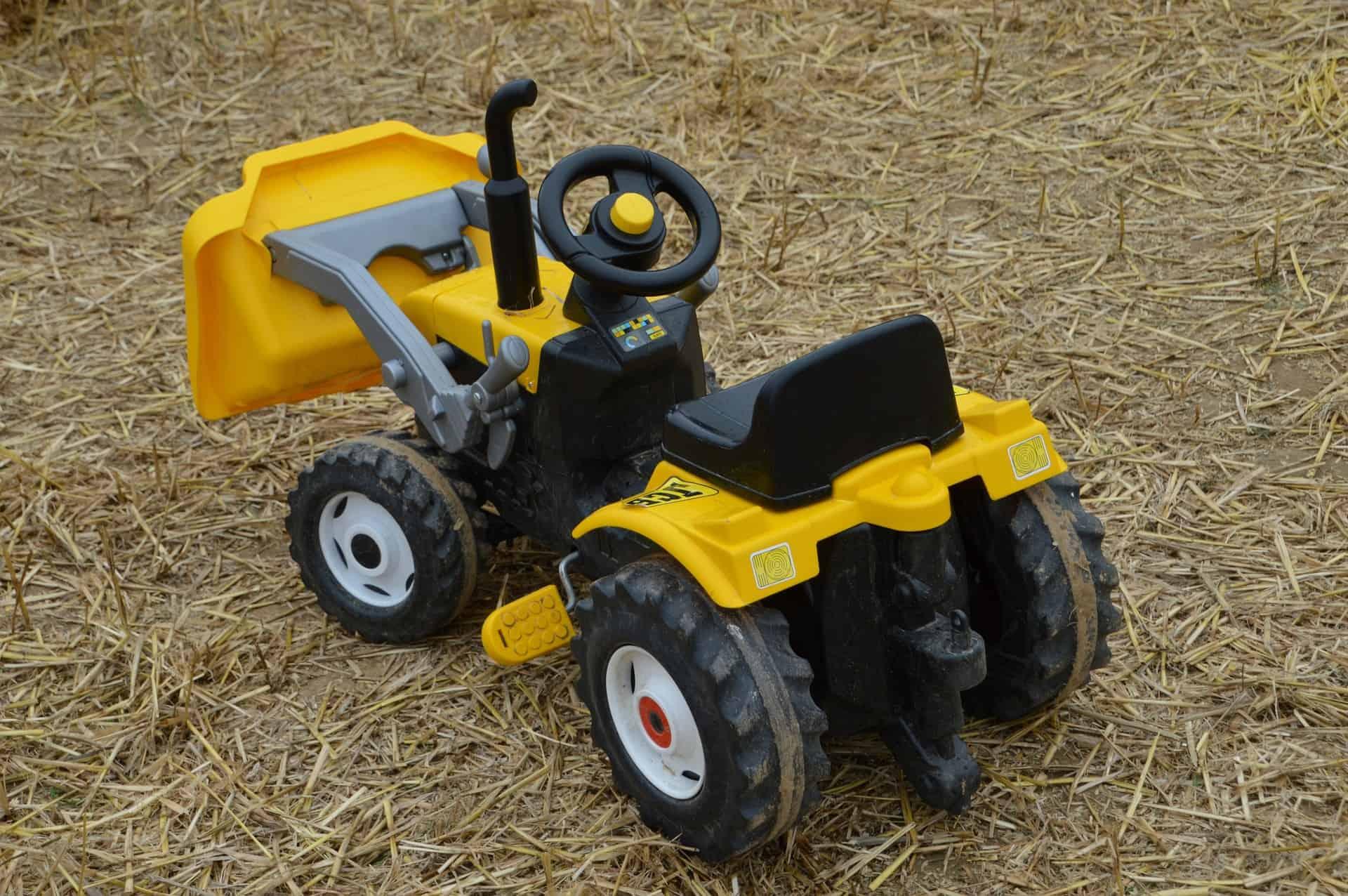 Imagem mostra um trator de brinquedo na grama.