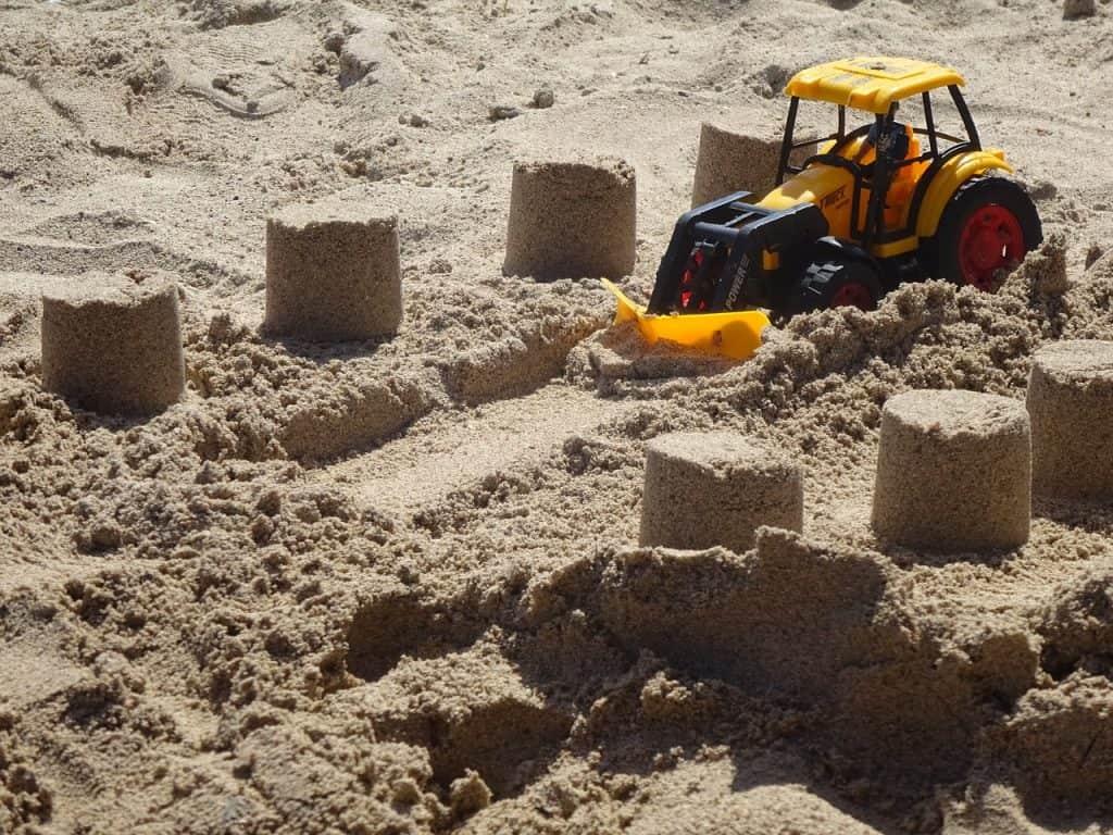 Imagem mostra um trator de brinquedo na areia.
