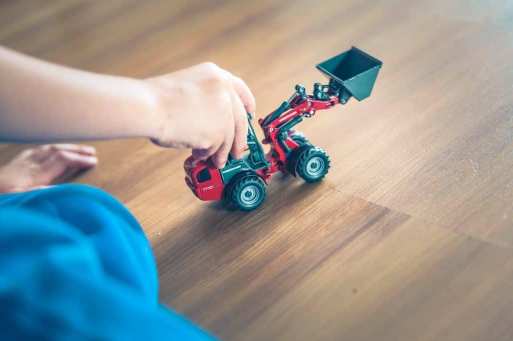 Imagem de criança brincando com trator vermelho e preto pequeno.