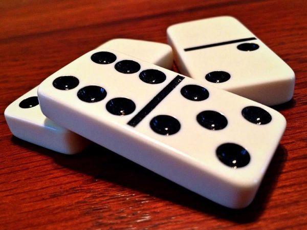 Imagem mostra um close de três peças de dominó sobrepostas, repousando em uma superfície de madeira.