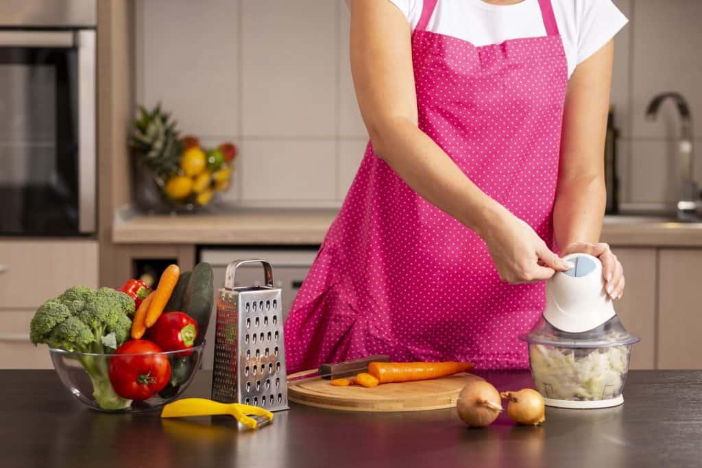 Imagem de mulher triturando vegetais.