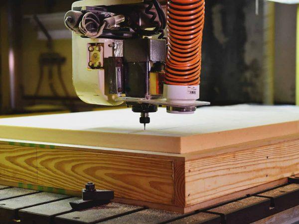 Imagem mostra o trabalho de uma tupia em um pedaço de madeira.