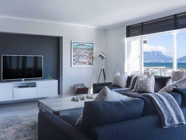 Na foto uma sala de estar com uma janela ampla, sofá azul, almofadas bege e uma televisão em cima de um móvel na frente de uma parede escura.