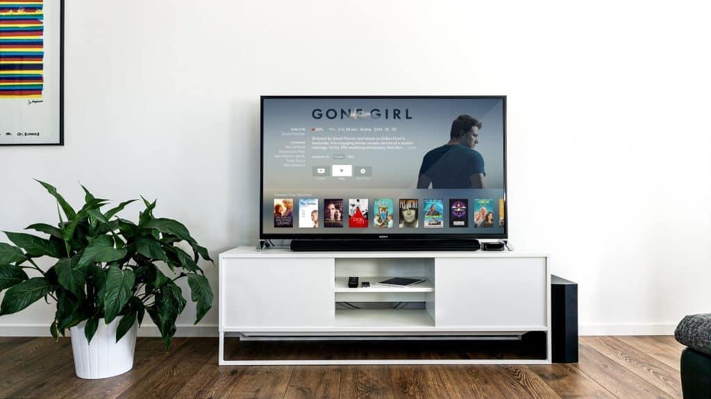Na foto uma televisão ligada em cima de um móvel branco com uma planta ao lado esquerdo em uma sala com piso de madeira.