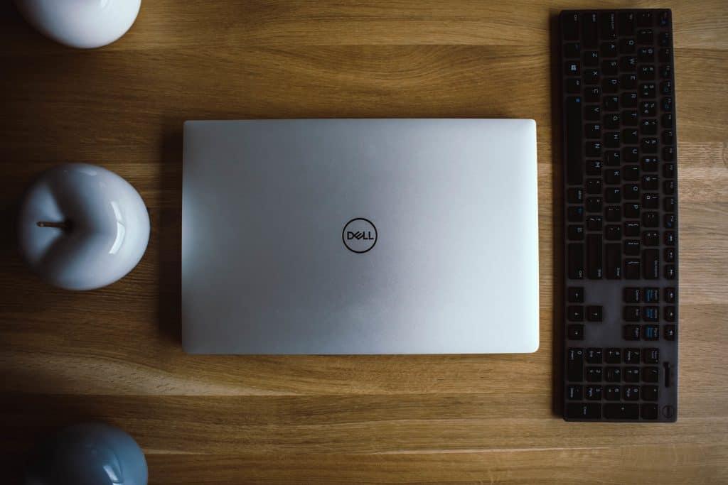 Imagem de um ultrabook cinza da dell fechado sobre mesa.