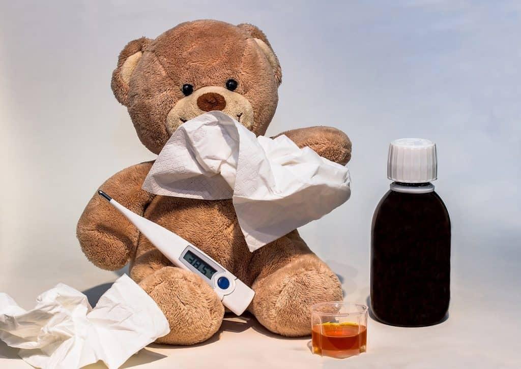 A imagem mostra ursinho de pelúcia sentado, com um termômetro digital encostado na sua barriga. O urso está com um lenço de papel próximo ao nariz e outro ao lado, no chão. Um frasco de xarope e um copinho medidor completam a imagem.