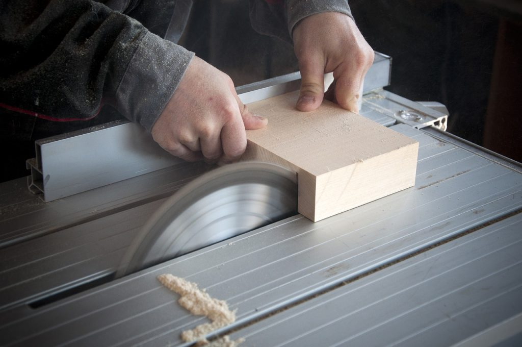 Mão cortando madeira com serra circular.