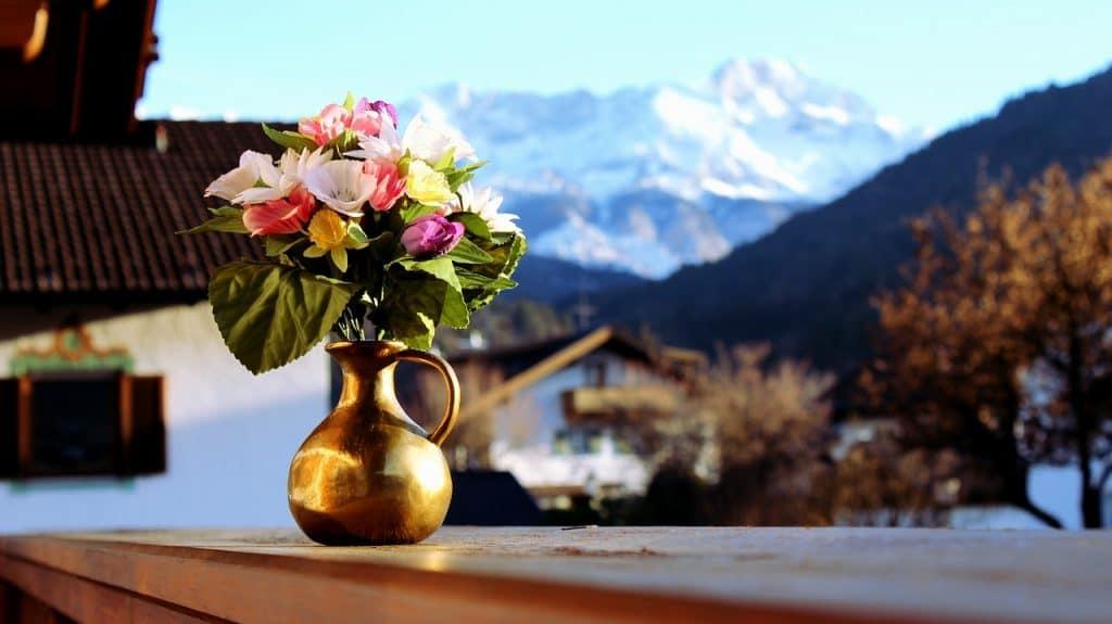 Vaso dourado com flores sobre muro e cidade com montanhas ao fundo.