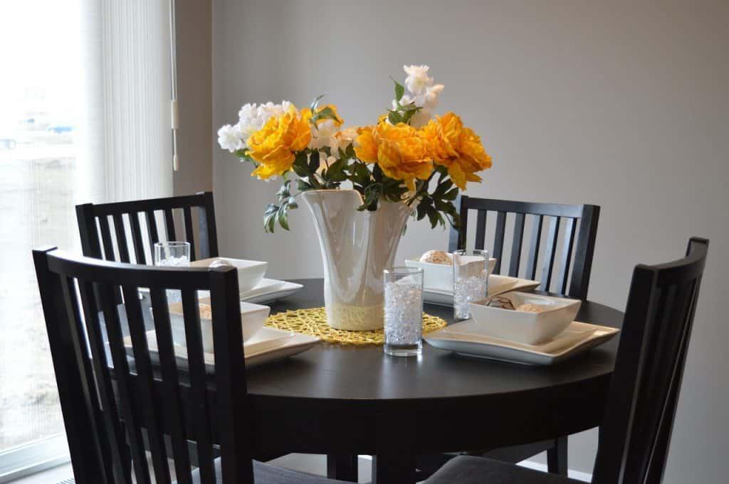 Vaso branco com flores sobre mesa de jantar de madeira escura.