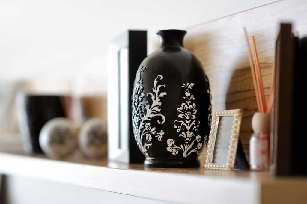 Imagem de vaso preto com decoração branca sobre móvel.
