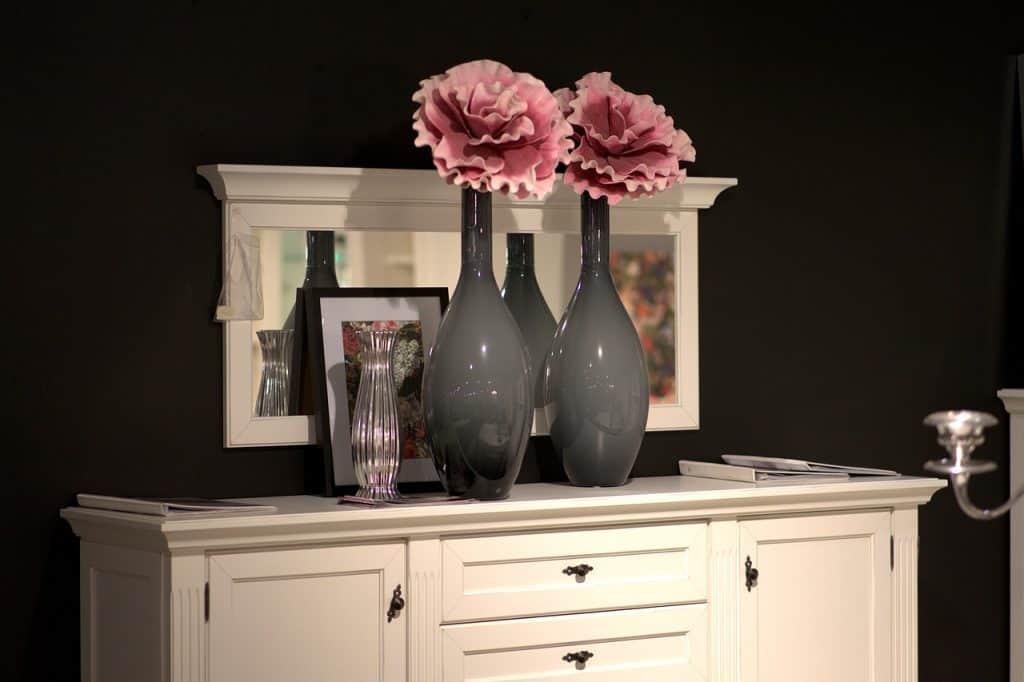 Dois vasos decorativos compridos, na cor cinza, com rosas artificiais, sobre aparador branco e quadro ao fundo.