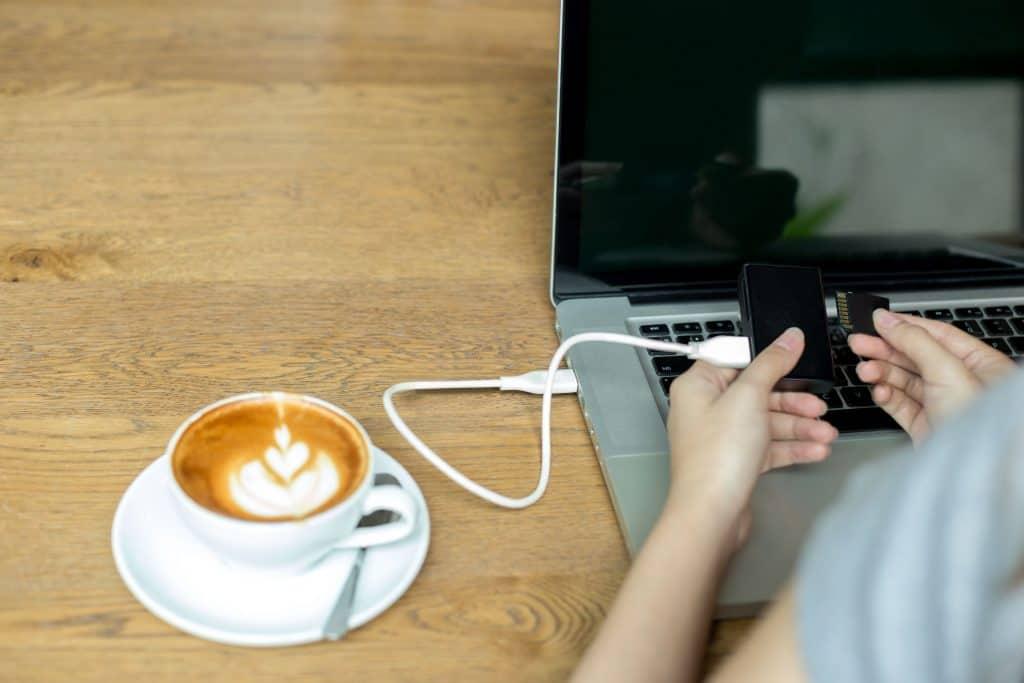 Imagem mostra uma pessoa usando um leitor de cartão de memória com uma xícara de café ao lado.