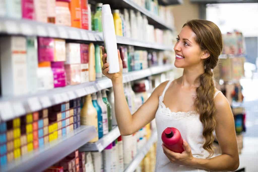 Imagem de mulher verificando embalagem de shampoo.