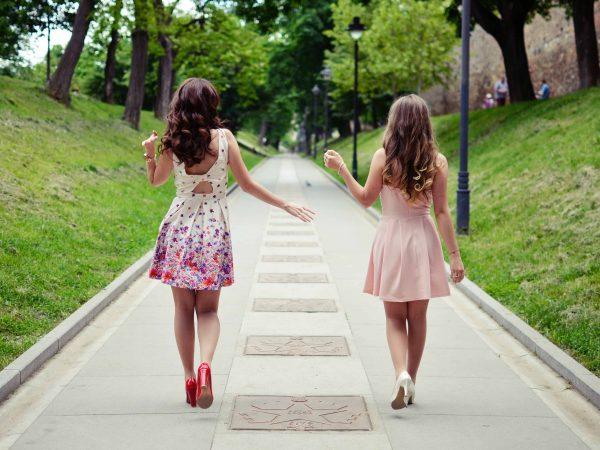 Foto de duas moças de costas, caminhando em uma calçada em meio a um espaço verde que se assemelha com um parque. Ambas vestem vestidos curtos, sapatos de salto e estão de cabelos soltos.