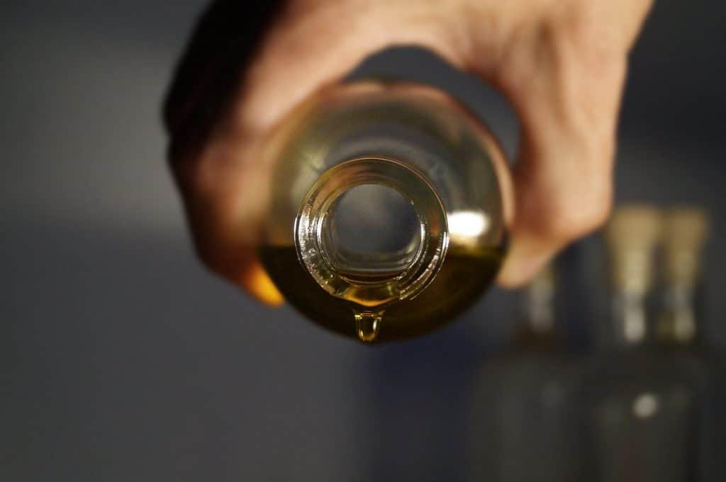 Mãos derramando óleo de vidro.