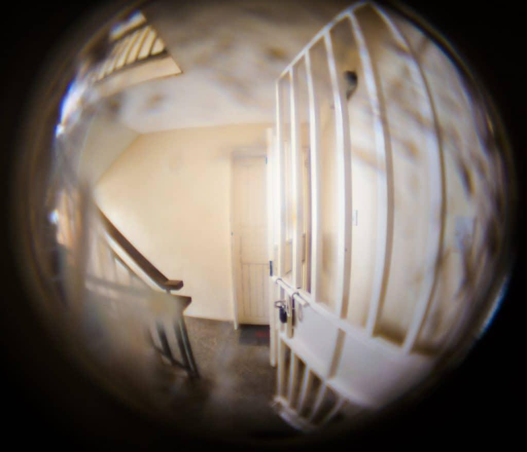 Visão do olho mágico do lado de dentro. É possível ver um portão branco e escadas.