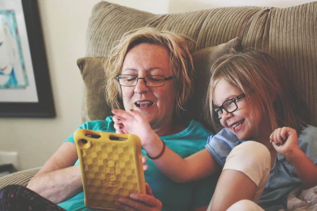 Foto de uma mulher idosa segurando um tablet com capa amarela, ao lado de uma menina pequena. Ambas estão sentadas em um sofá e sorrindo.