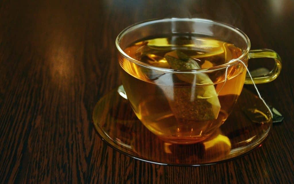 Imagem de xícara de vidro com infusor de chá sobre mesa de madeira.