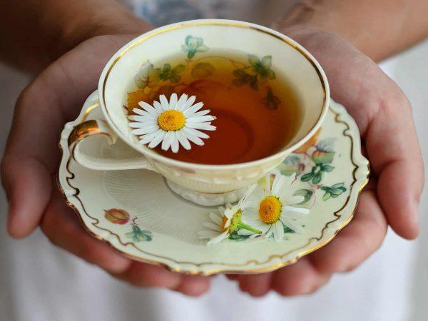 Imagem de pessoa servindo uma xícara de chá com margarida.