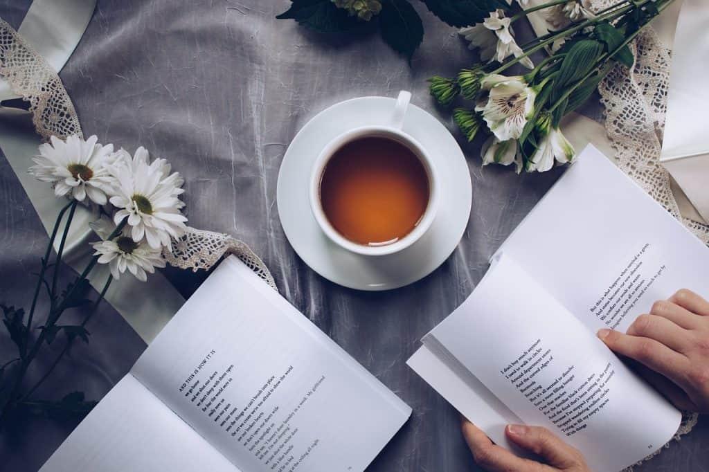 Imagem de pessoa lendo com livros sobre a mesa, flores e xícara de chá branca com pires.