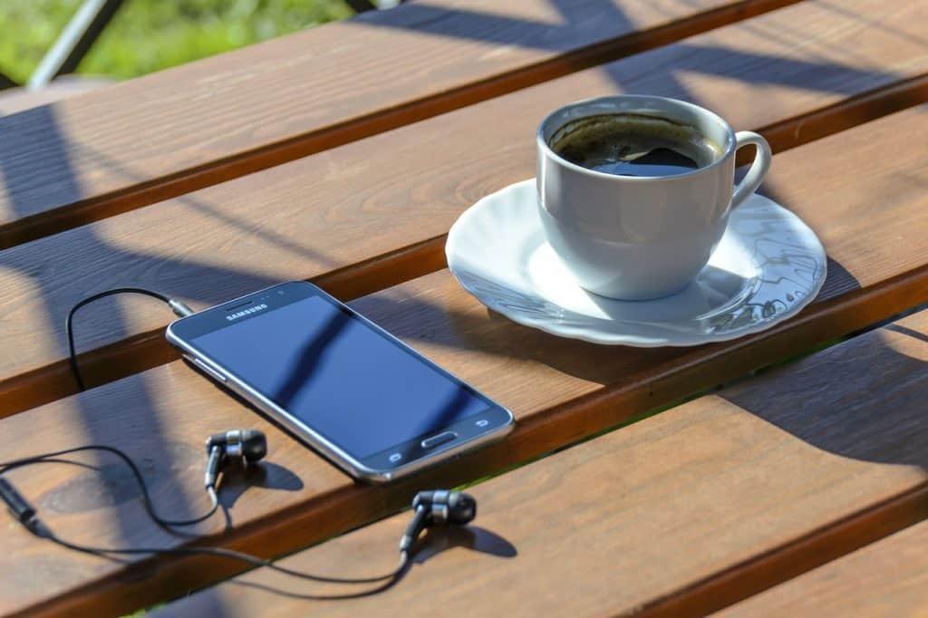 Imagem de celular com fone de ouvidos Samsung sobre mesa de madeira ao lado de xícara de café.