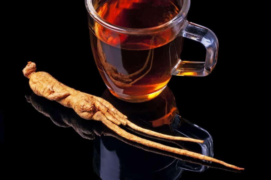 Xícara de chá e raiz de ginseng ao lado.