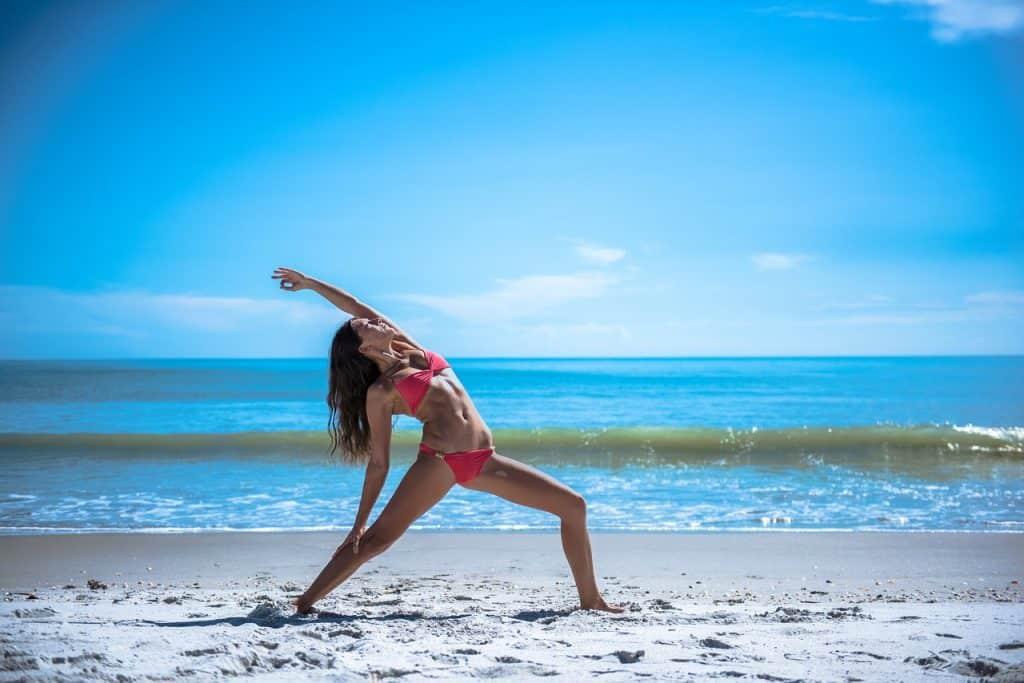 Imagem de mulher praticando ioga na praia.