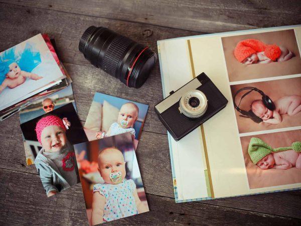 Na foto um álbum de fotos com algumas fotos de bebê espalhadas e uma lente de câmera.