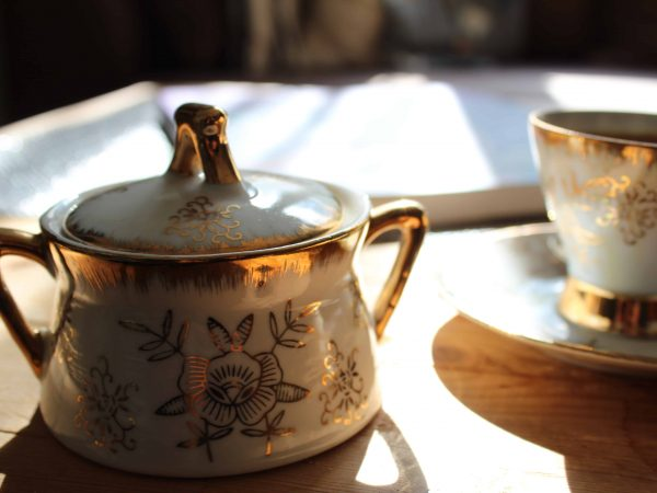Açucareiro e xícara de porcelana com detalhes dourados sobre uma mesa.