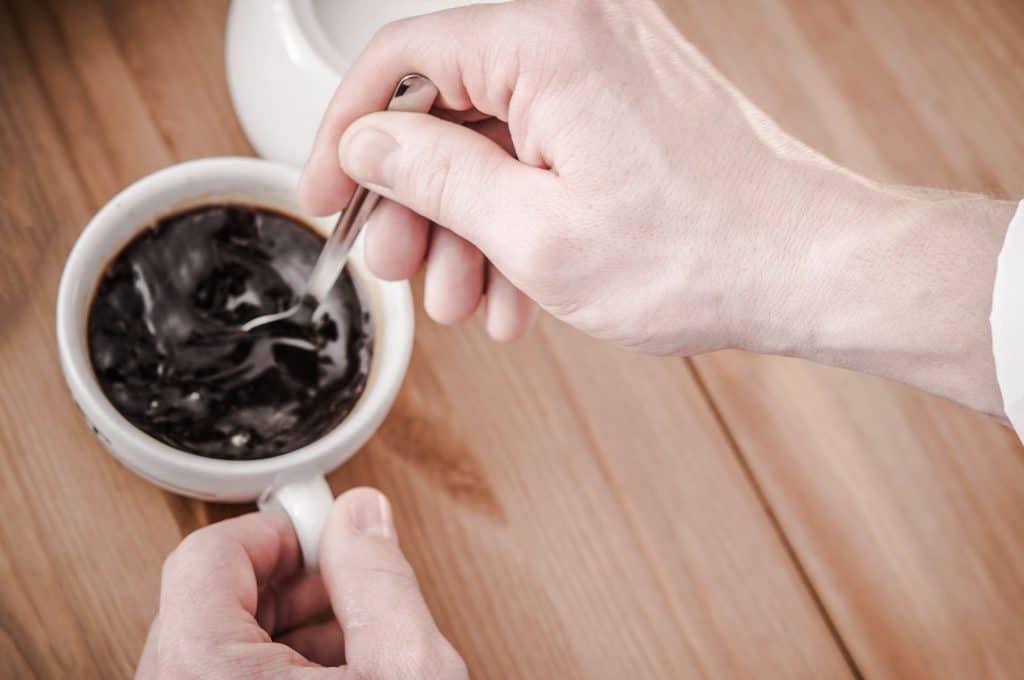 Mão masculina adoçando uma xícara de café preto.