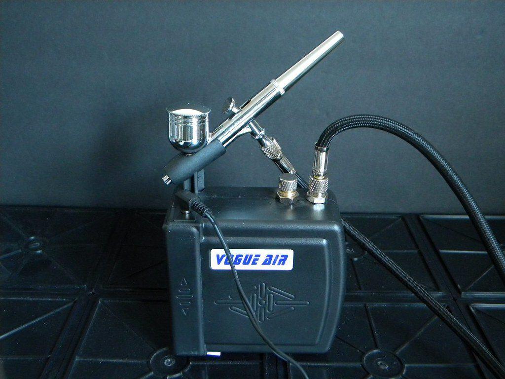 Imagem de um compressor de ar conectado a um aerógrafo.