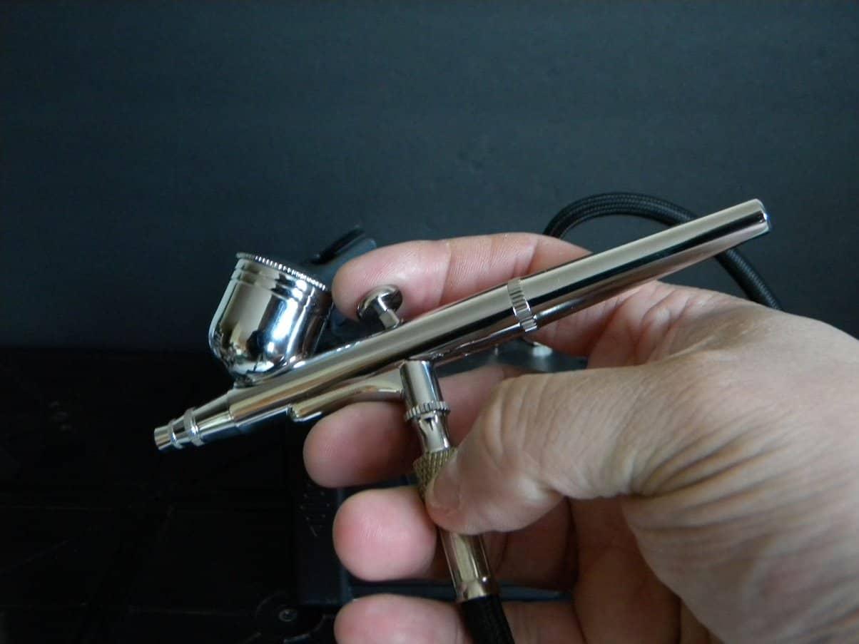 Imagem de uma mão segurando um aerógrafo de dupla ação.