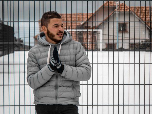 Imagem mostra um homem vestindo agasalho encostado em uma cerca.