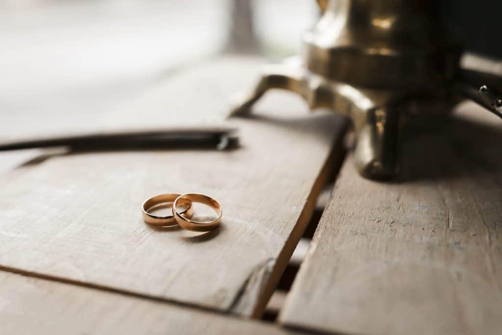 Imagem com duas alianças sob uma superfície de madeira.