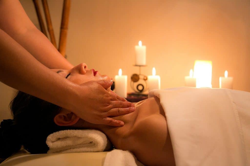 Imagem de mulher recebendo massagem em spa com velas aromáticas acesas ao fundo.