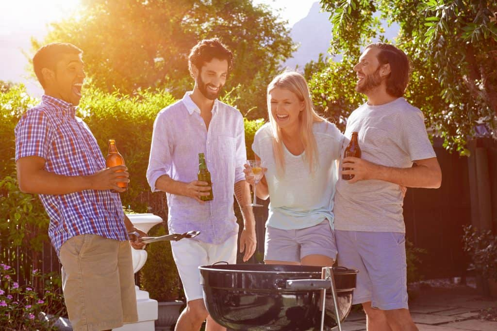 4 pessoas em um jardim ao redor de uma churrasqueira sem fumaça, sorrindo e com garrafa de cerveja na mão.