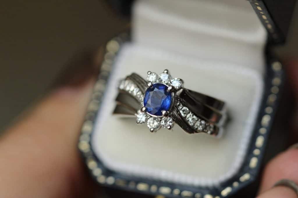 Na foto um anel com pedra azul e incolor.