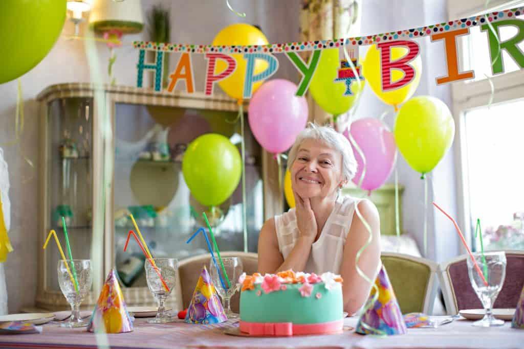 Na foto uma senhora em uma festa de aniversário.