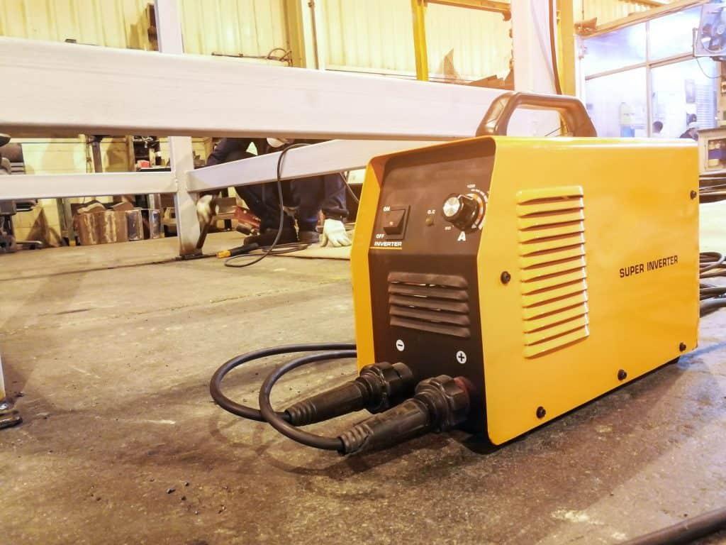 Imagem mostra uma máquina de solda preta e amarela.
