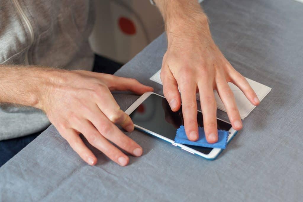 Na foto um homem limpando a tela de um celular.