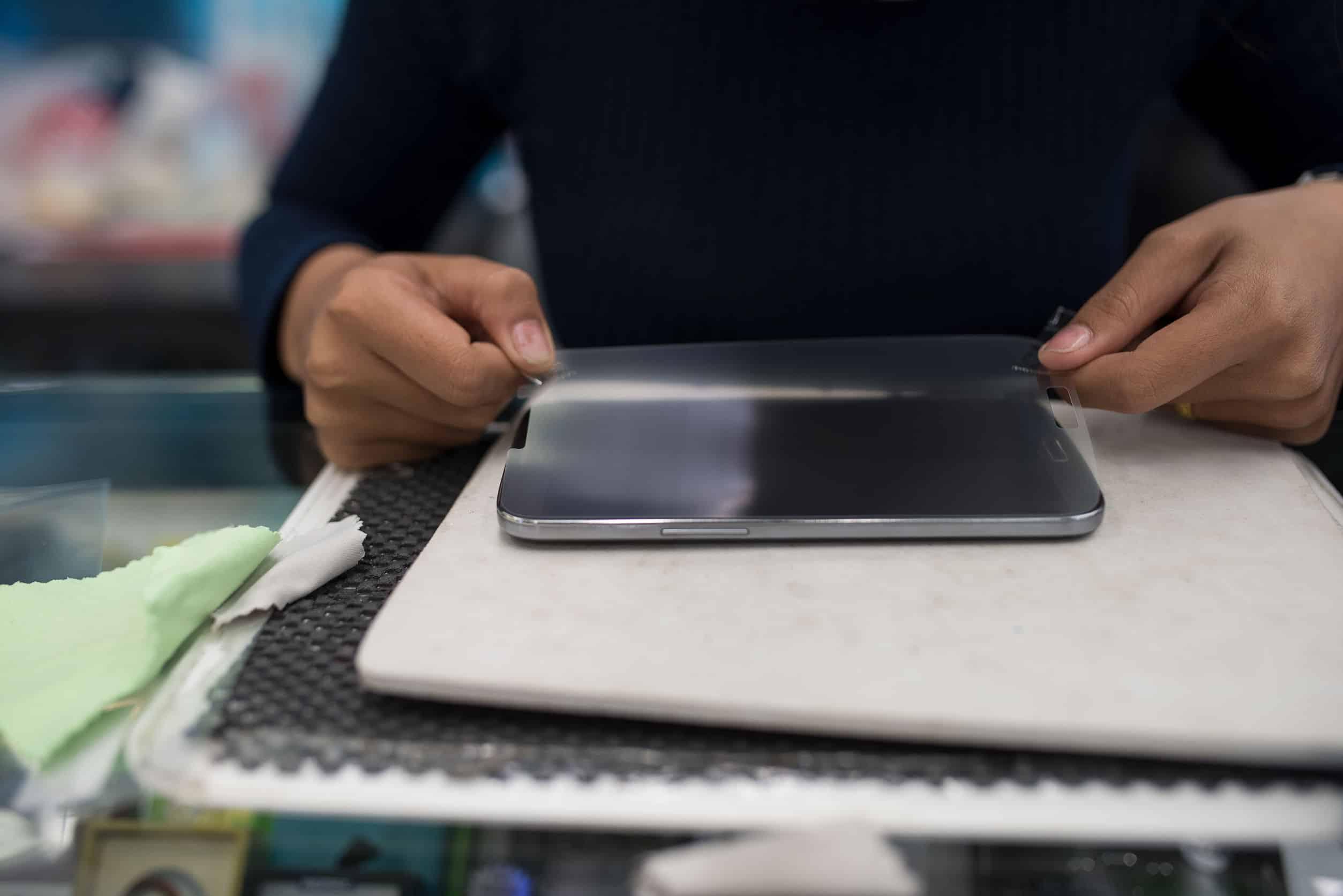 Imagem de pessoa aplicando película de vidro em um celular.