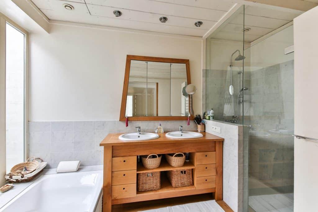 Banheiro com bancada da pia de madeira, box com chuveiro.