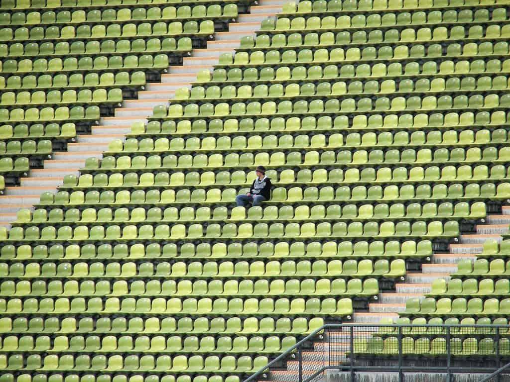 Imagem mostra um rapaz, sozinho, sentado em uma cadeira, enquanto todas as outras em volta estão vazias.