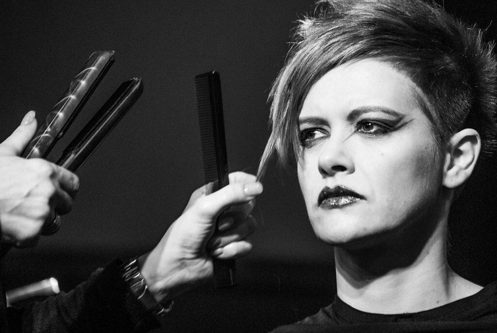 Foto em preto e branco de cabeleireiro alisando o cabelo de uma modelo com uma chapinha.