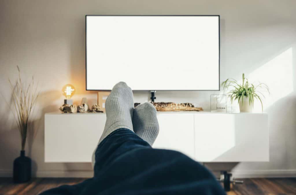 Foto que ponto de vista do modelo, mostrando suas pernas esticadas e cruzadas e os pés com meia. Ao fundo, um rack com uma TV.