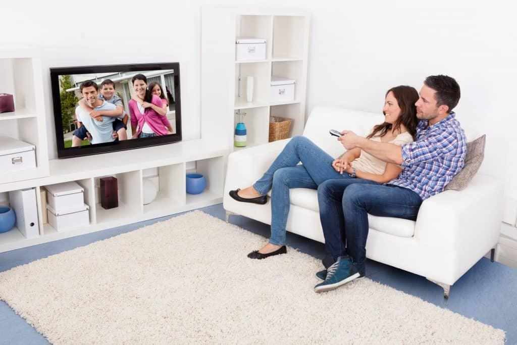 Imagem de casal sentado em sofá assistindo TV.