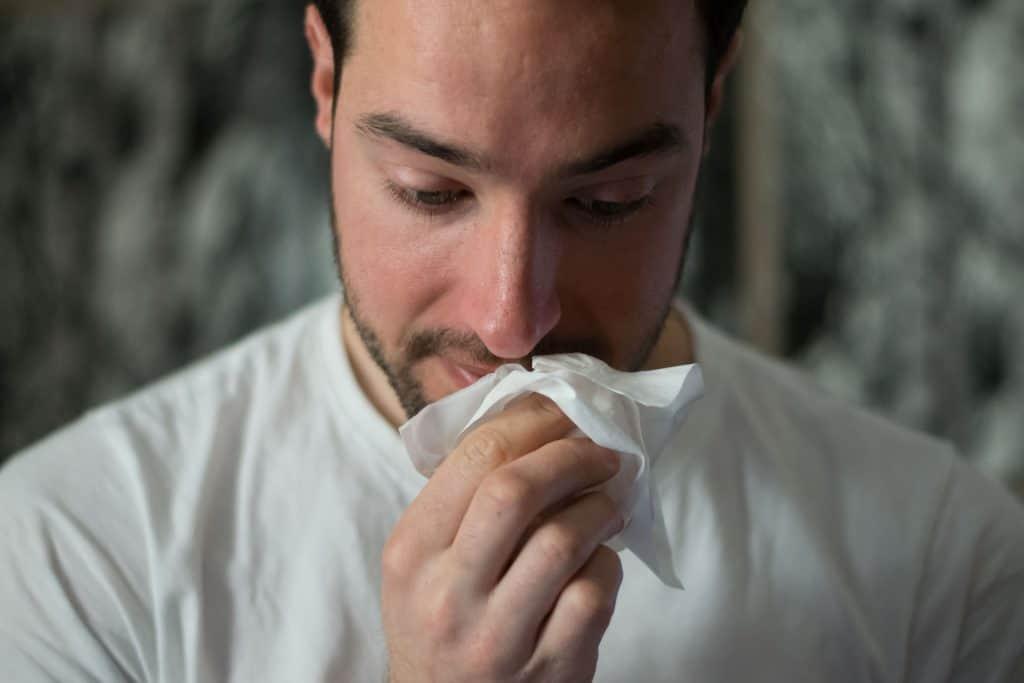 Imagem de um homem assoando o nariz.