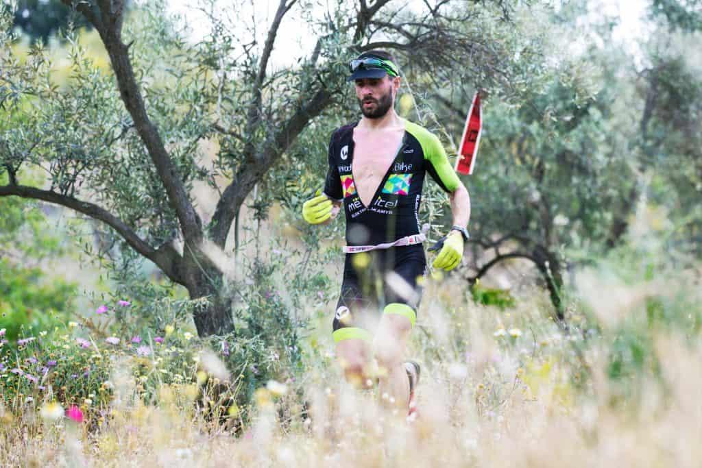 Imagem mostra um homem em meio à uma corrida campestre, usando um traje de corrida e um boné.