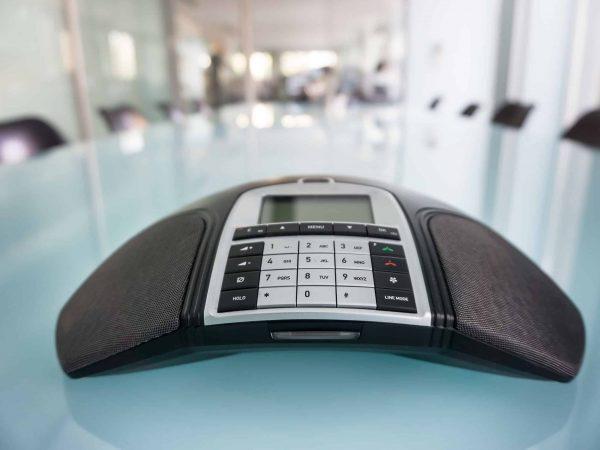 Na foto um aparelho de audioconferência em cima de uma mesa de reuniões em uma sala vazia.