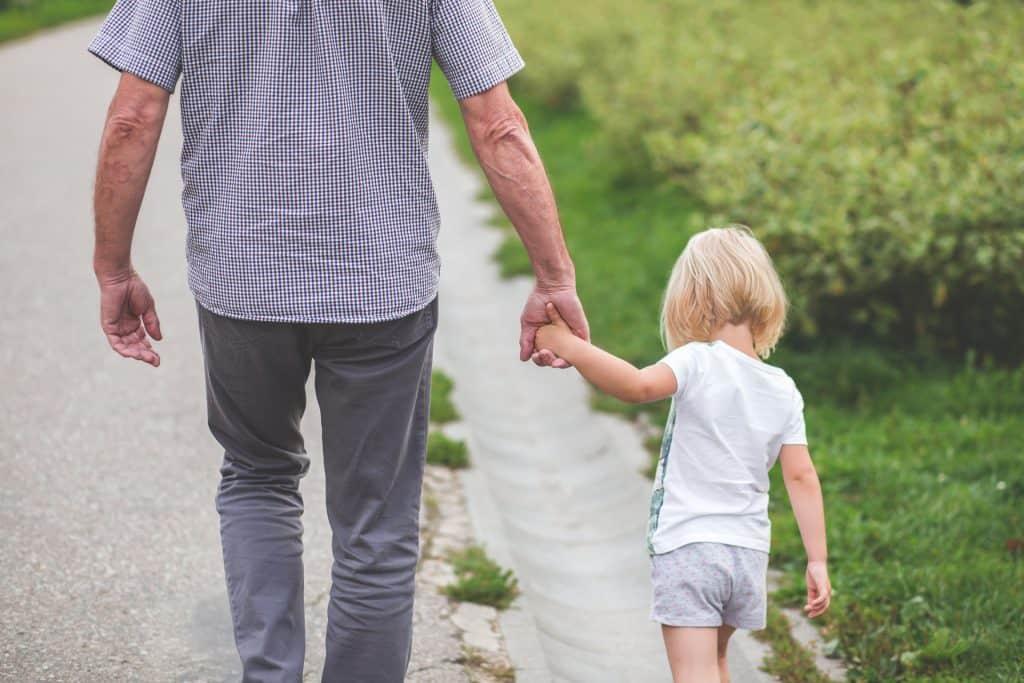 Na foto um senhor andando de mãos dadas com uma criança.